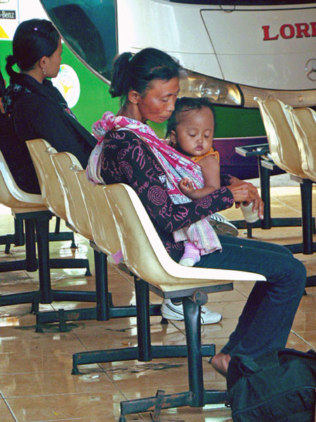 Mother and child wait in the bus terminal in Denpasar, Bali.