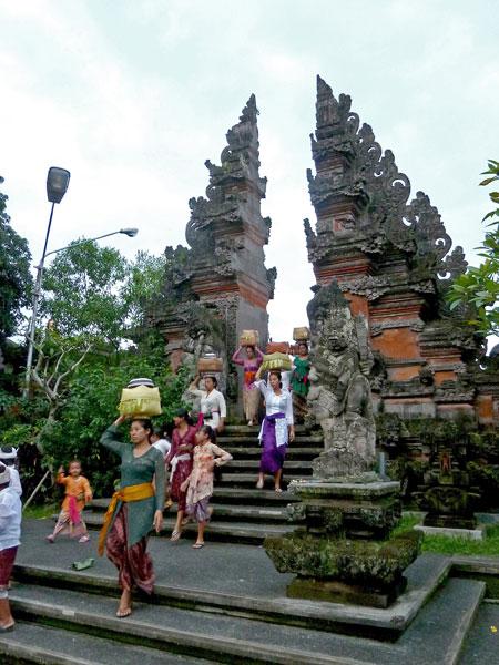 Balinese emerge from a Hindu temple ceremony at Pura Dalem Puri in Peliatan, Bali.