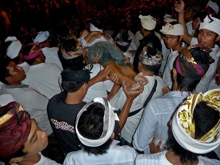 A body is carried to the stage at Pura Dalem Puri in Peliatan, Bali.