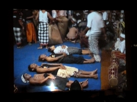 A Jumbotron view of bodies on stage at Pura Dalem Puri in Peliatan, Bali.