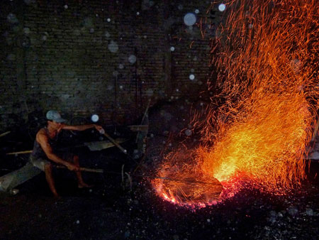 A worker raises hellfire and brimstone at the gamelan factory in Bekonang, Java.