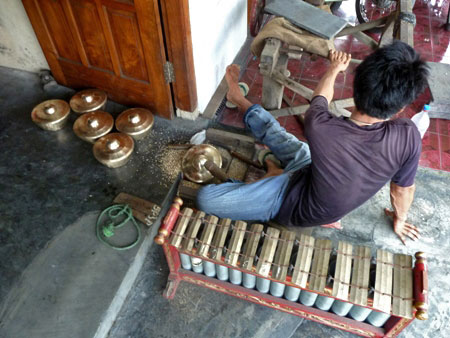 A worker goofs off at the gamelan factory in Bekonang, Java.