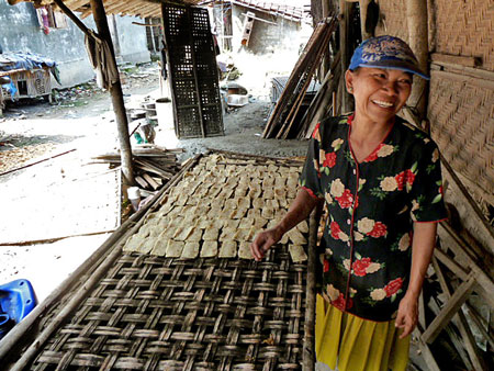 A woman has fun at work in a small rice cracker factory in Solo, Java.