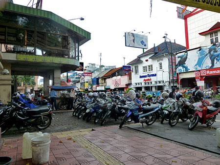 A restaurant overhangs some motorcycles on Jalon Malioboro in Yogyakarta, Java.
