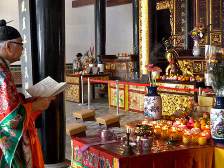 A priest conducts a Buddhist prayer service at the Thian Hock Keng Temple in Chinatown, Singapore.