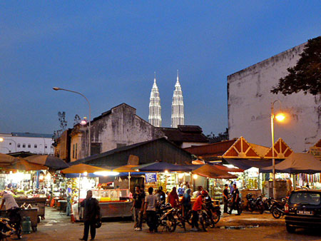The Chow Kit market lights up the night as the Petronas Towers loom in Kuala Lumpur, Malaysia.