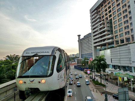 The KL Monorail cruises at dusk in Kuala Lumpur, Malaysia.