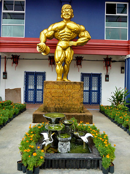 A golden statue of the number one bodybuilder in Chinatown, Melaka, Malaysia.