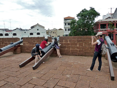Some Japanese tourists climb on cannons in Melaka, Malaysia.