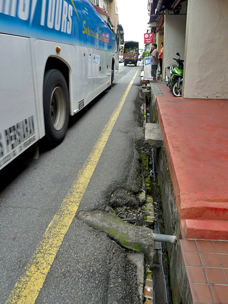 A standard sidewalk, or lack thereof, in Melaka, Malaysia provides a perfect opportunity to get hit by a bus.