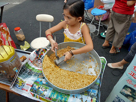 A mother and daughter team up to serve sweet, homemade treats as a night market begins in Chinatown, Melaka, Malaysia.