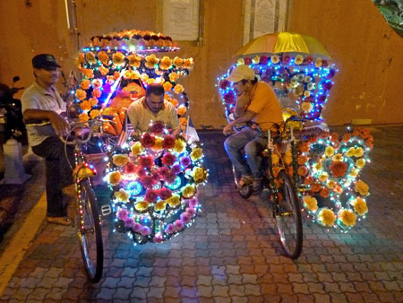 A couple of trishaw drivers light up the night in Chinatown in colorful Melaka, Malaysia.