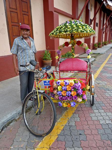A very flowery trishaw in Chinatown, Melaka, Malaysia.