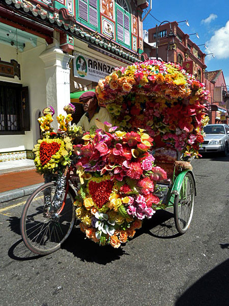 A psychedelic trishaw brightens the day in Melaka, Malaysia.