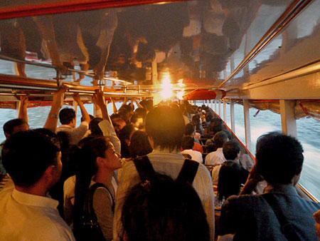 The Chao Phraya river taxi packed at rush hour in Bangkok, Thailand.