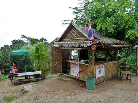 A nice lady who sells drinks and gasoline by the roadside above Laem Singh, Phuket, Thailand.