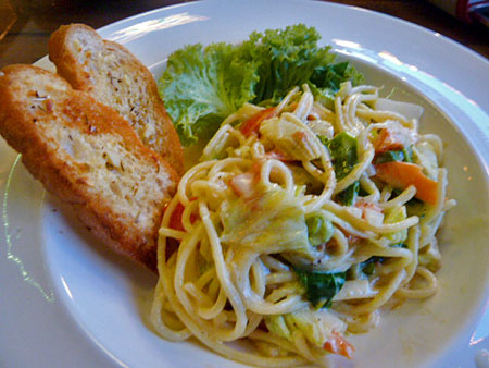 A plate full of pasta and garlic bread gets ready to enter my mouth in Phuket Town, Thailand.