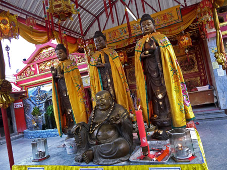 Four locals hang out at Put Jaw Temple in Phuket Town, Thailand.