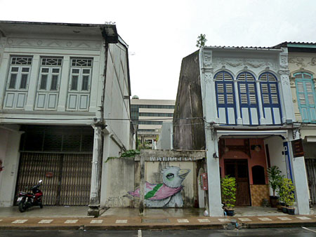 A big bird hangs out between two 19th century Sino-Portuguese shophouses in Phuket Town, Thailand.