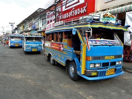 Three songthaews wait for fares in Phuket Town, Thailand.