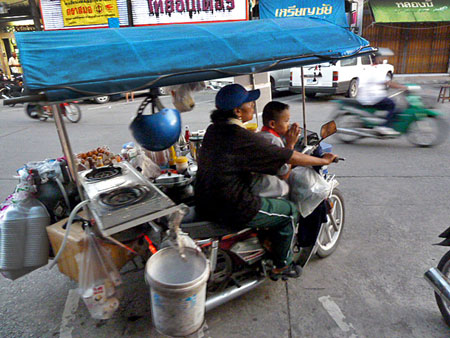 A tuk-tuk food cart pulls away in Phuket Town, Thailand.