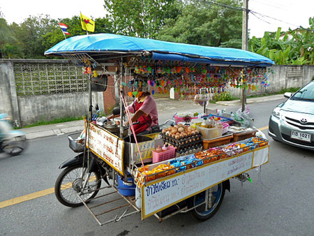 A food stall on a tuk-tuk flies by in Phuket Town, Thailand.