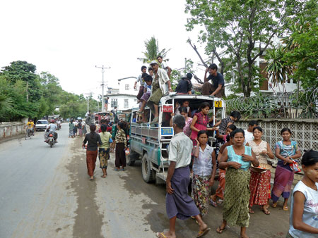 A horde of locals bails off of a standardly overloaded pickup in Mandalay, Myanmar.