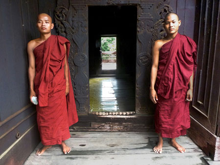A pair of young Buddhist monks stand guard at Shwe In Bin Kyaung monastery in Mandalay, Myanmar.