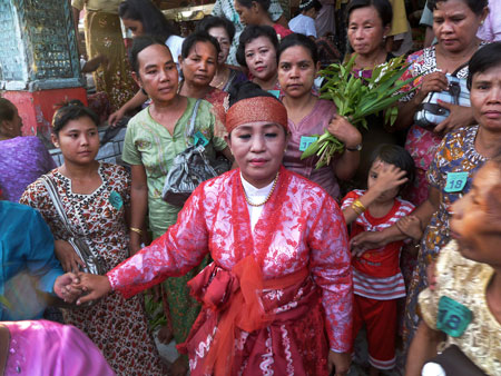 Post-performance, a nat kadaw exits the main temple with her entourage at the nat pwe in Taungbyone, Myanmar.
