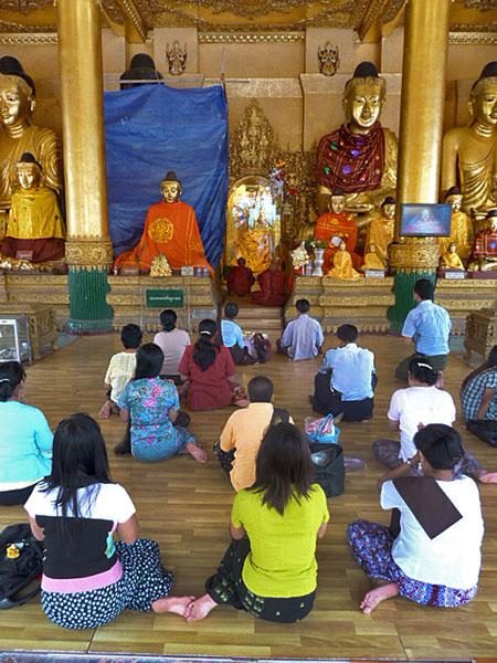 The faithful pray in a Buddhist shrine at Shwedagon Pagoda in Yangon, Myanmar.