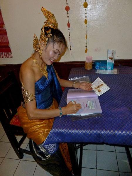 May Kaidee signs copies of her cookbook at her restaurant in Banglamphu, Bangkok, Thailand.