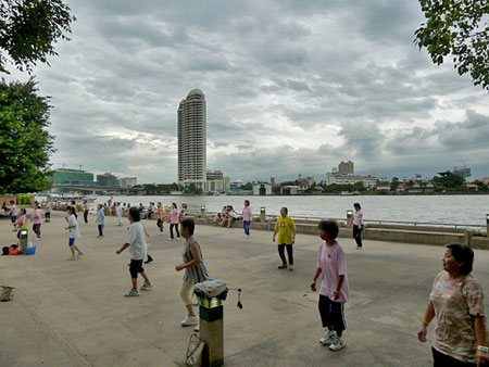 A late evening aerobics session steams full ahead at Santichaiprakan Park in front of the Chao Phraya river in Banglamphu, Bangkok, Thailand.