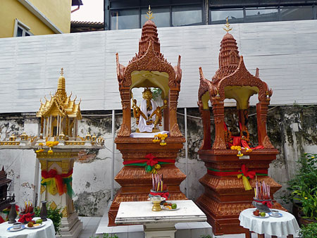 A couple of Thai spirit houses sit in front of a hotel on Thanon Khao San in Banglamphu, Bangkok, Thailand.