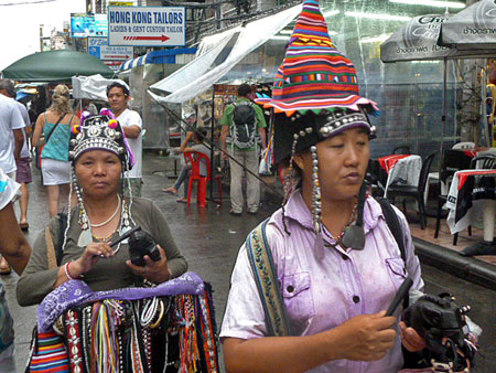 A couple of Thai hill tribe hawkers make their way down Thanon Khao San in Banglamphu, Bangkok, Thailand.
