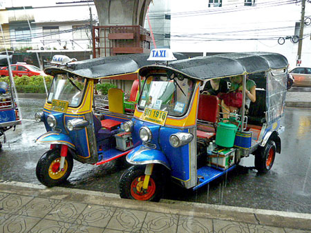 Two tuk-tuks take up space in front of a tourist trap in Banglamphu, Bangkok, Thailand.