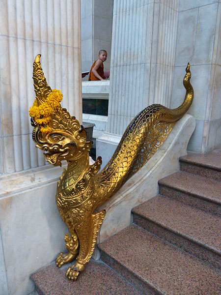 A novice Buddhist monk and a dragon guard the entrance to Wat Bowoniwes in Banglamphu, Bangkok, Thailand.