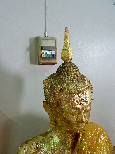 Layers of gold leaf peel from the face of a Buddha image at Wat Chana Songkhram in Banglamphu, Bangkok, Thailand.