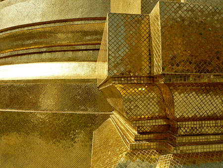 Close-up of the gold tiles of the Phra Siratana Chedi glowing in the afternoon sun at the Temple of the Emerald Buddha in Bangkok, Thailand.