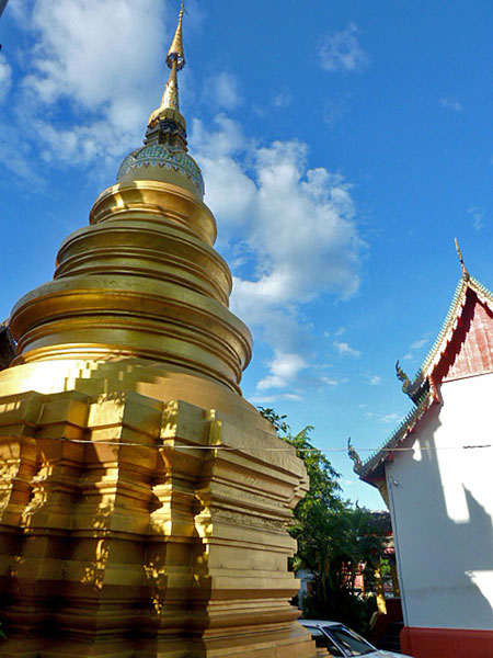 A golden chedi glints in the sun at Wat Sai Mun Muang Temple in Chiang Mai, Thailand.