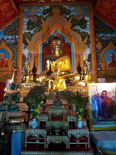 Quad Buddhas bathed in soft light at Wat Thung Yu Temple in Chiang Mai, Thailand.