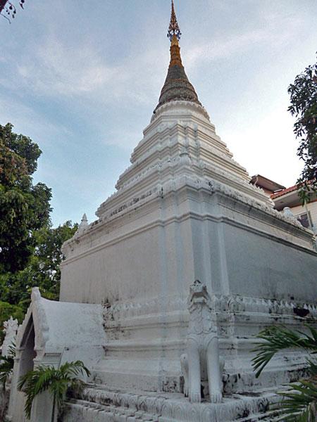 A white chedi lies hidden in back at Wat Thung Yu Temple in Chiang Mai, Thailand.