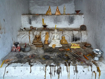 A small, crusty Buddhist shrine at Wat Thung Yu Temple in Chiang Mai, Thailand.