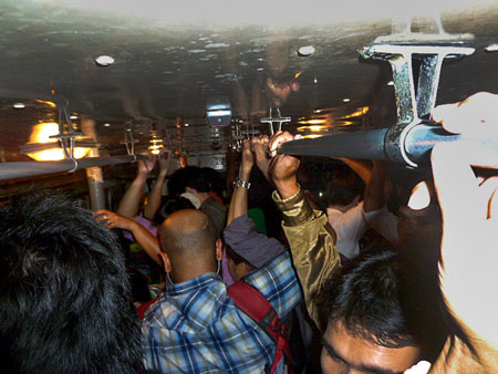 A packed night on bus 15 in Bangkok, Thailand.