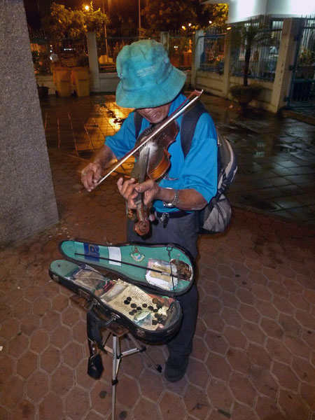 A violinist saws away near the Sathorn stop on the Chao Phraya river in Bangkok, Thailand.