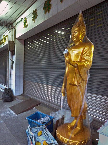Plastic Buddha meets plastic shrinkwrap in Bangkok, Thailand.