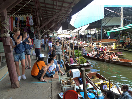 The full-blown daily tourist frenzy gathers steam at the floating market in Damnoen Saduak, Thailand.