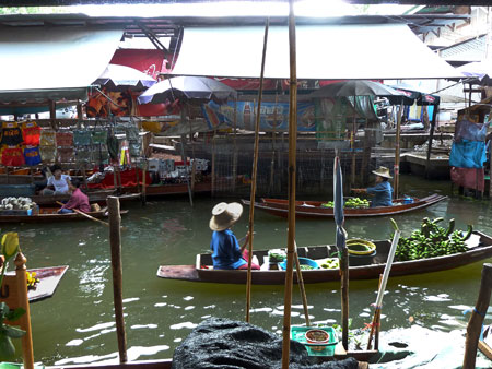 Early birds ply the waterways at the floating market in Damnoen Saduak, Thailand.