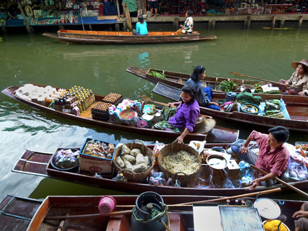 Chock-full boats gently bob at the floating market in Damnoen Saduak, Thailand.