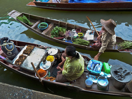 Coconut and fruit vendors at the floating market in Damnoen Saduak, Thailand.