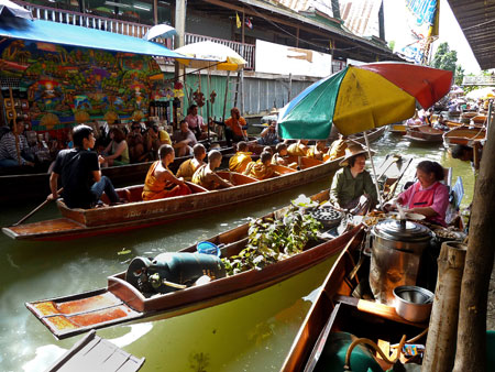 The epitome of calm cruises through chaos, as Buddhist monks enjoy the floating market in Damnoen Saduak, Thailand.